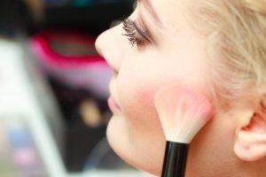 woman applying light pink blush