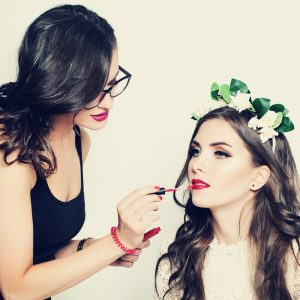 makeup artist applying lipstick to client