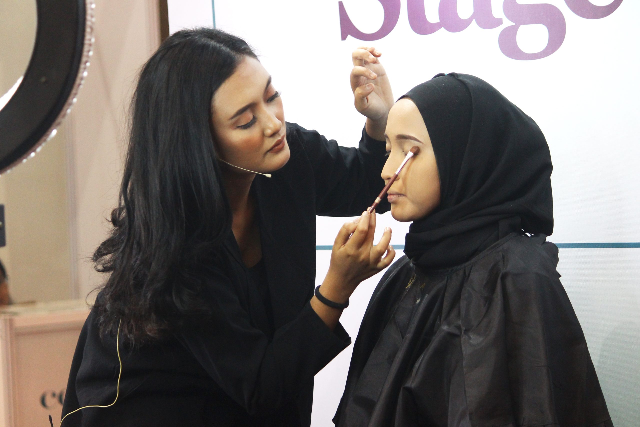 woman applying makeup to another woman